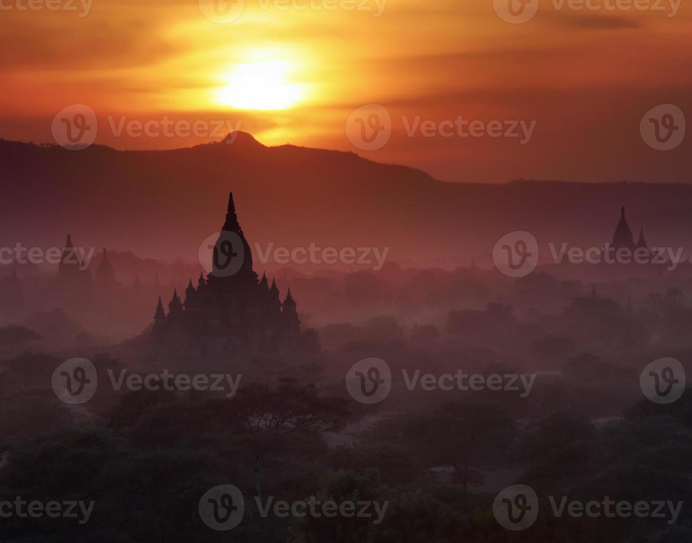 Puesta de sol sobre niebla bagan, myanmar foto