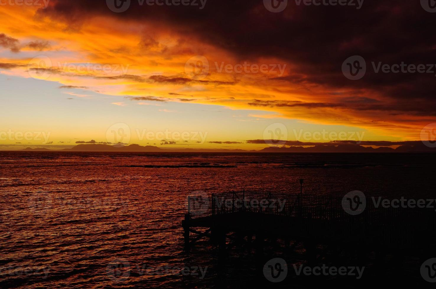 puesta de sol solar detrás de Cape Point a través de la bahía falsa. foto