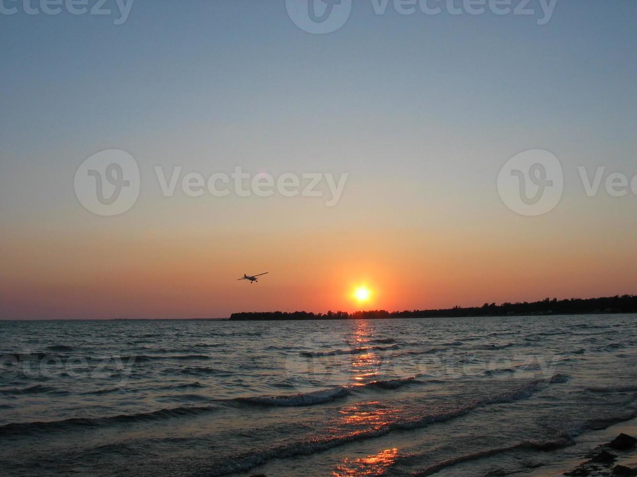 avión hacia la puesta de sol foto