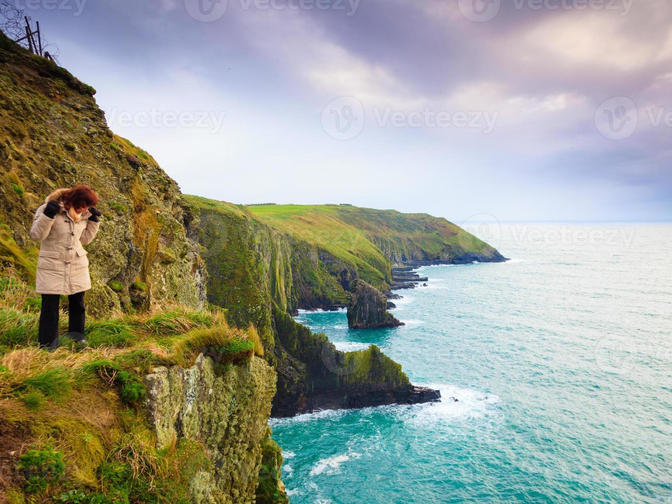 costa atlántica irlandesa. mujer turista de pie sobre un acantilado de roca foto