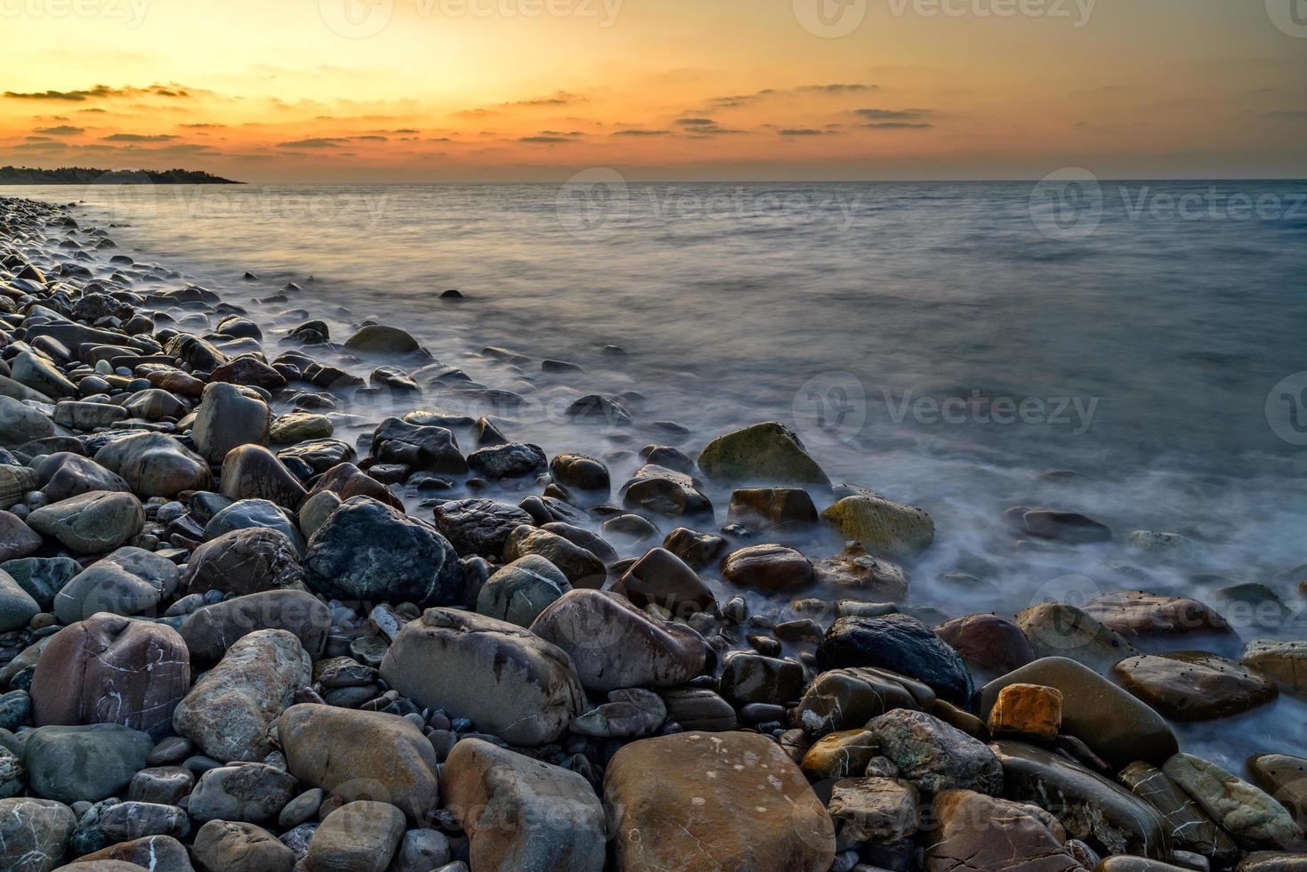 puesta de sol sobre la playa de guijarros foto