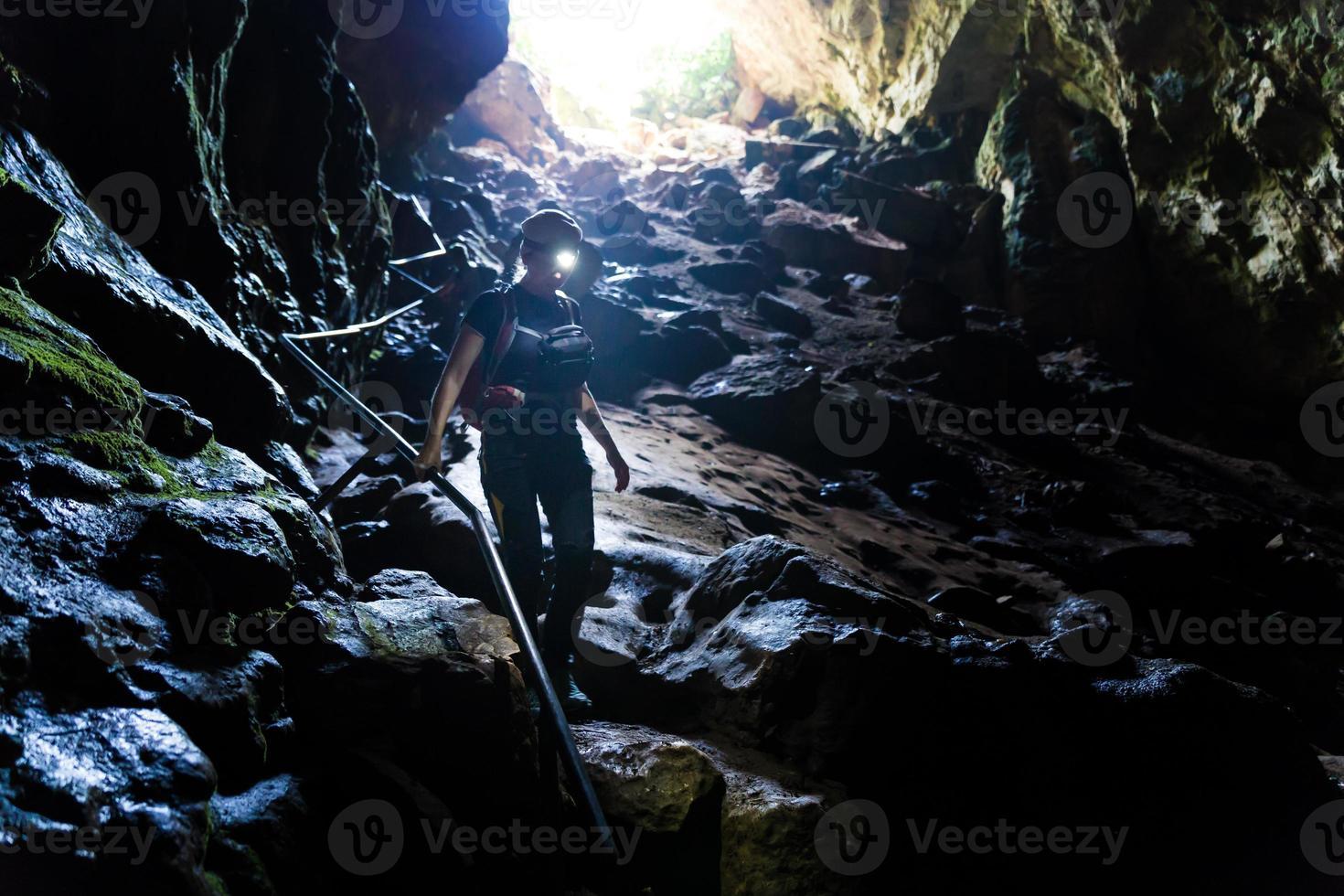 mujer caminando por la cueva de piedra con faro. foto