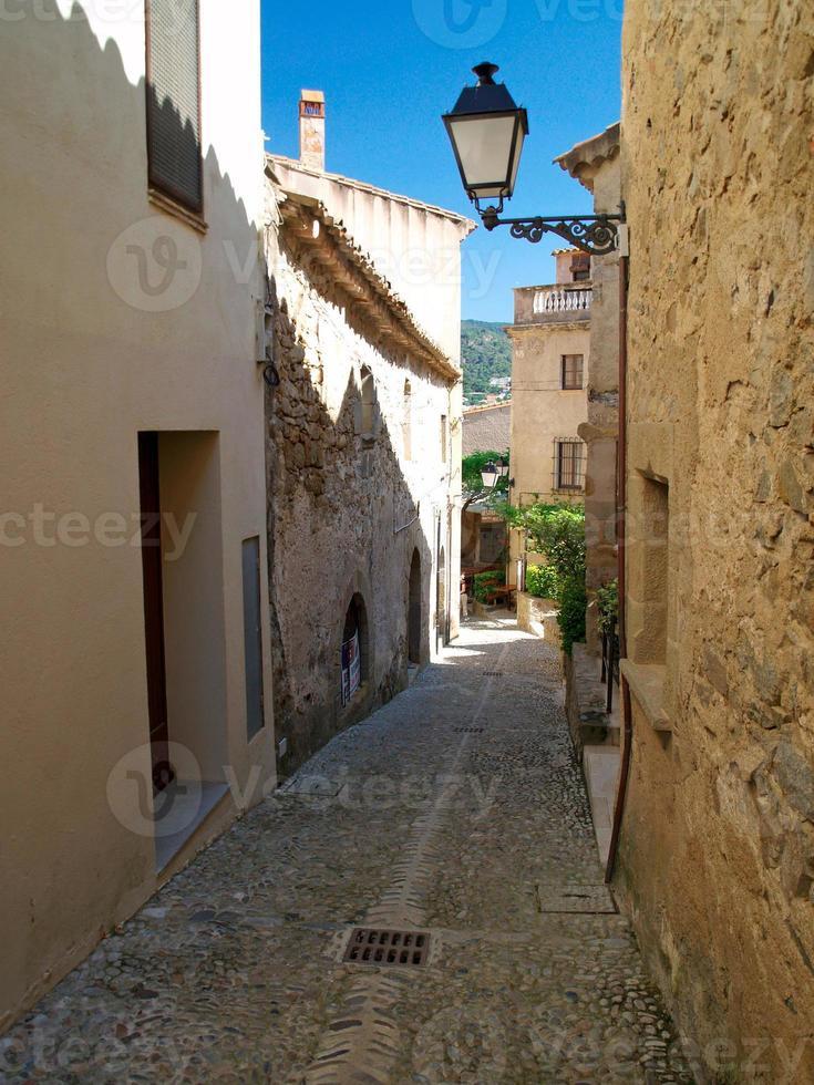 Calle estrecha en la ciudad española - Tossa de Mar foto