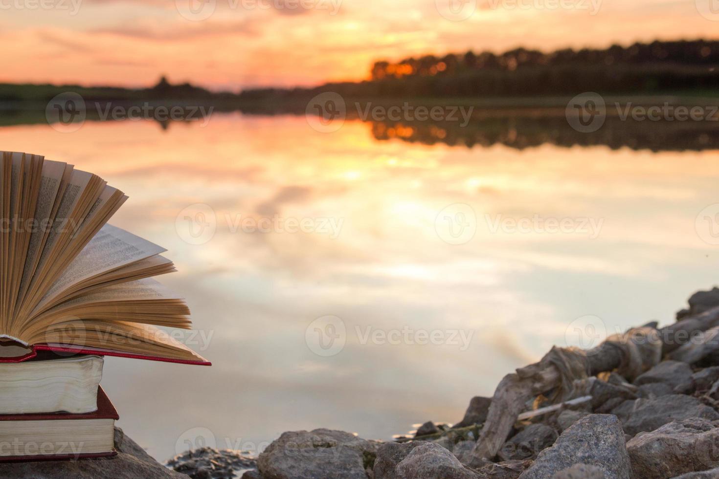 Stack of hardback book, Open  book on blurred nature landscape photo