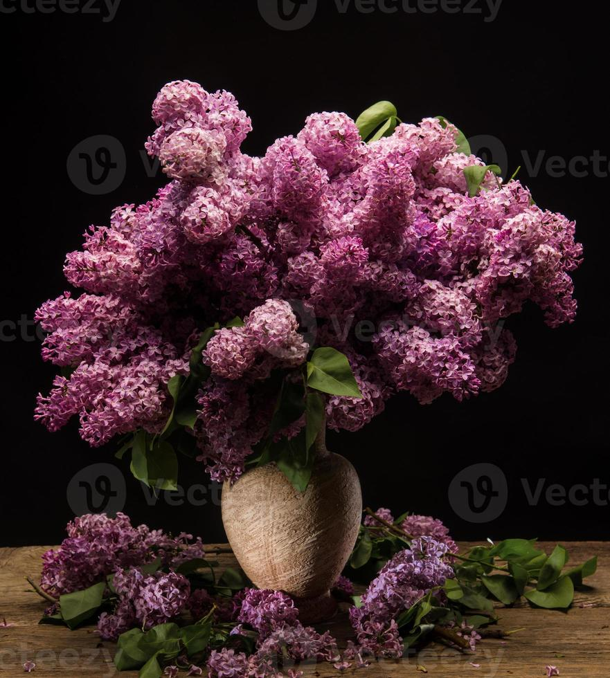 Blooming branches of lilac in vase photo