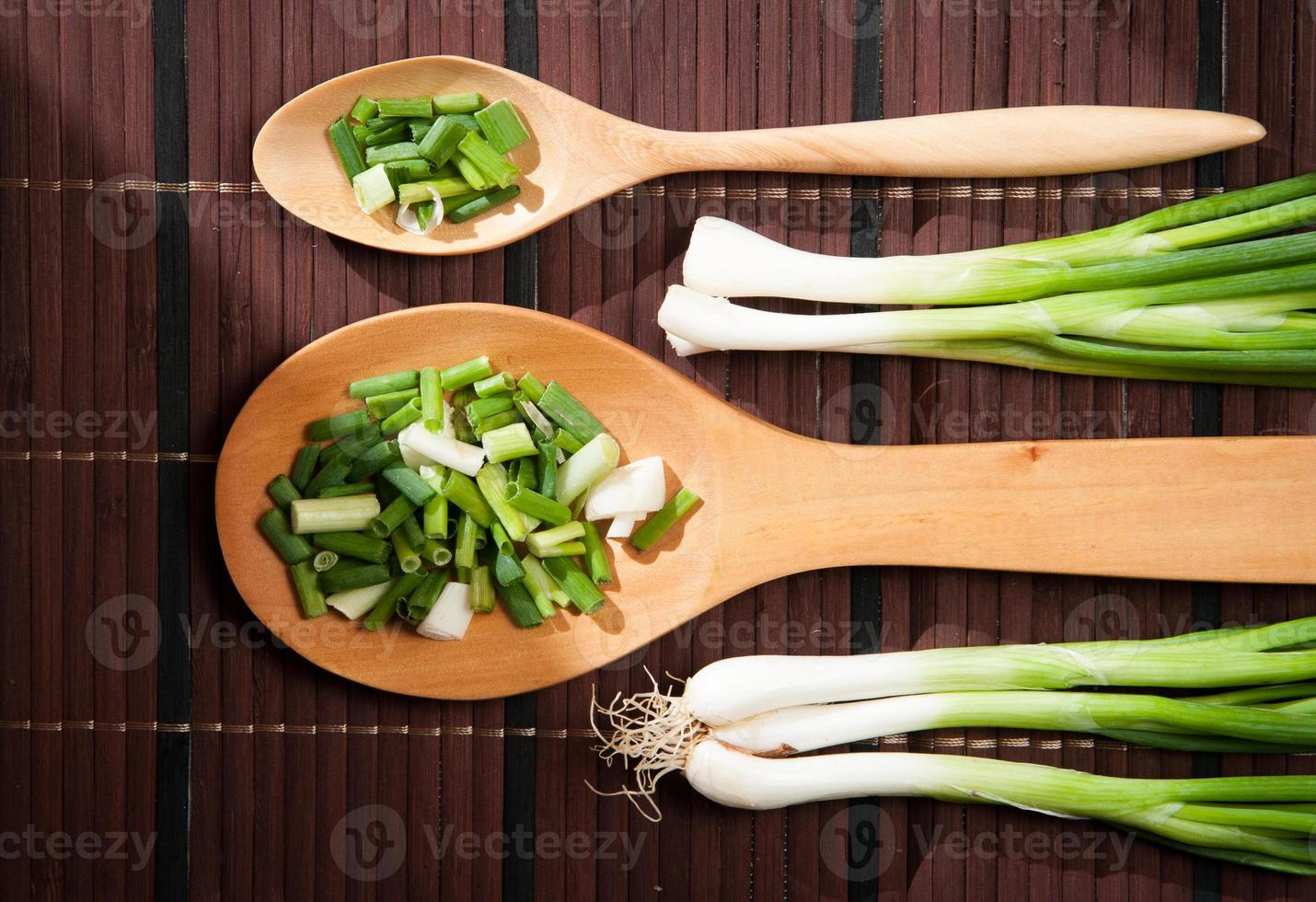 Chopped green  onions and spoon photo