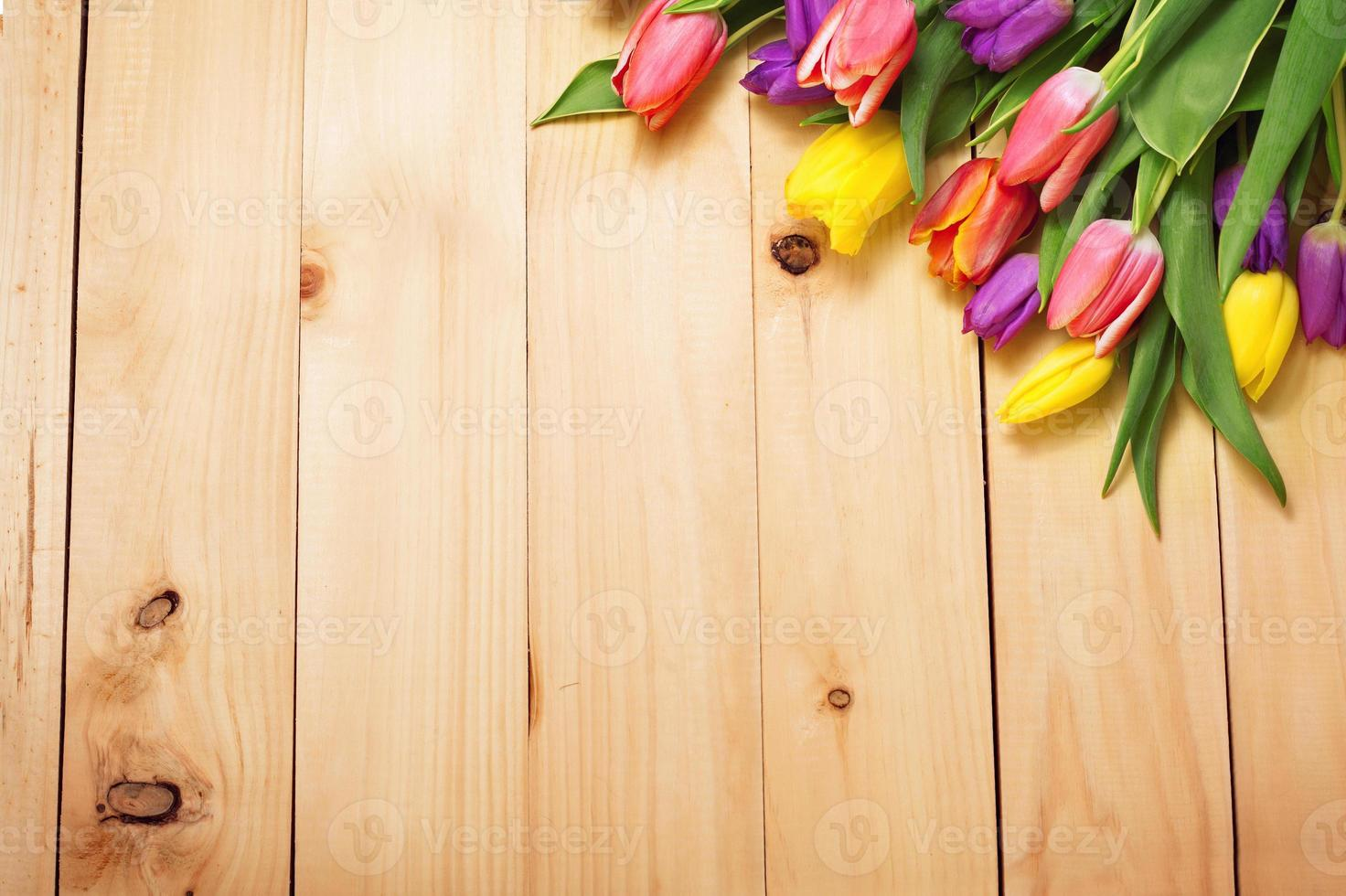 Spring Flowers bunch at wood floor texture. Beautiful Tulips bou photo