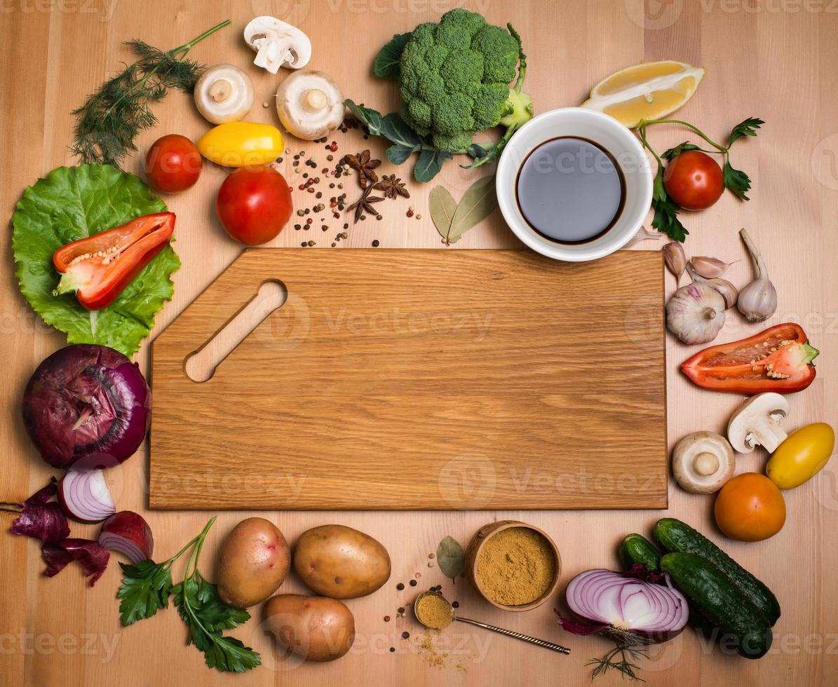Various vegetables and spices around empty cutting board. Top view. photo