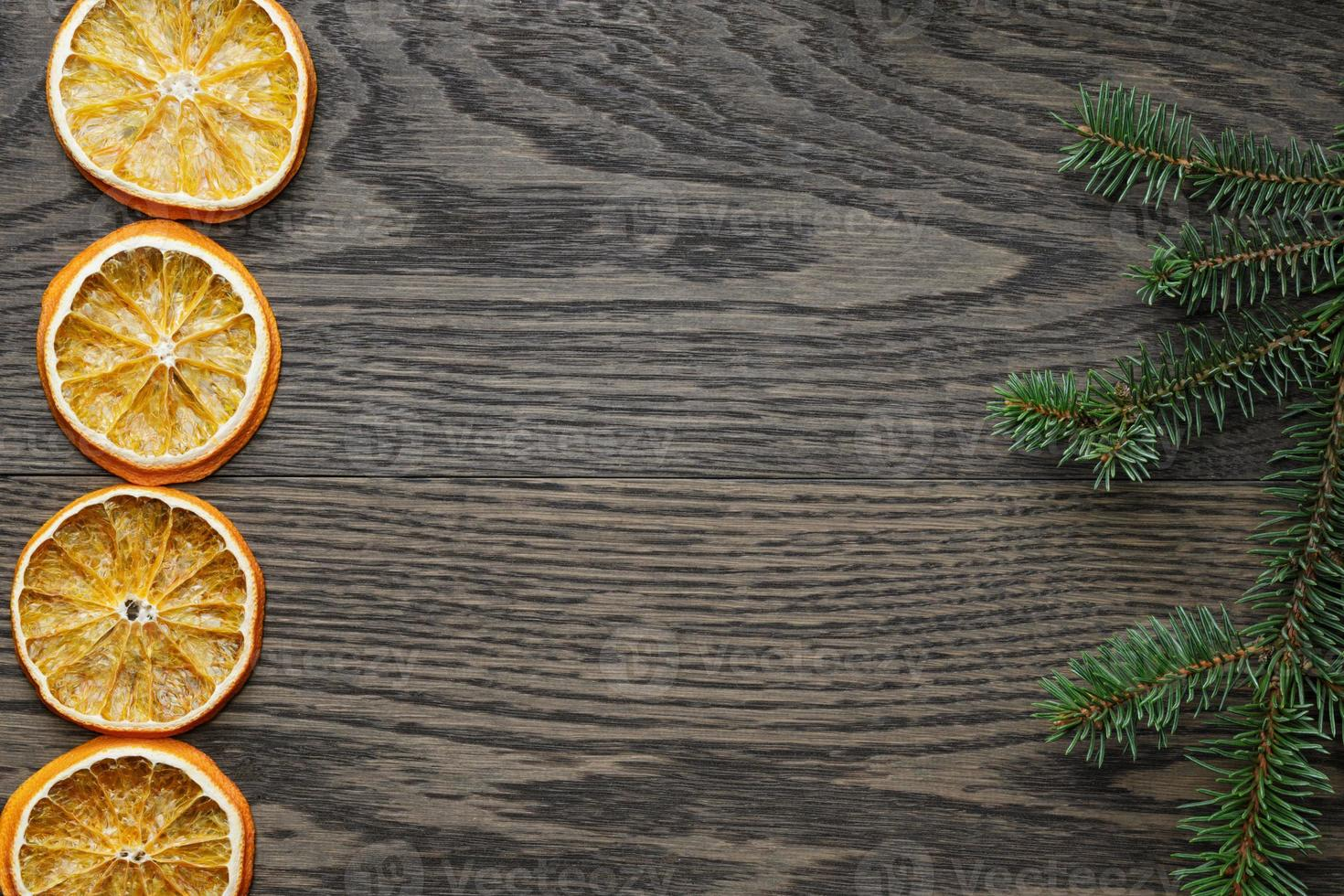 spruce twig with dried orange slices on oak table photo