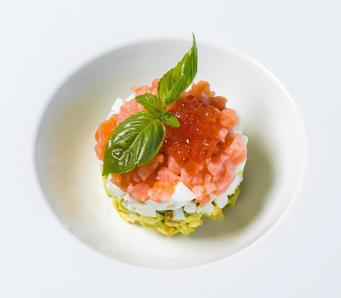 Comida de caviar rojo en un plato blanco foto