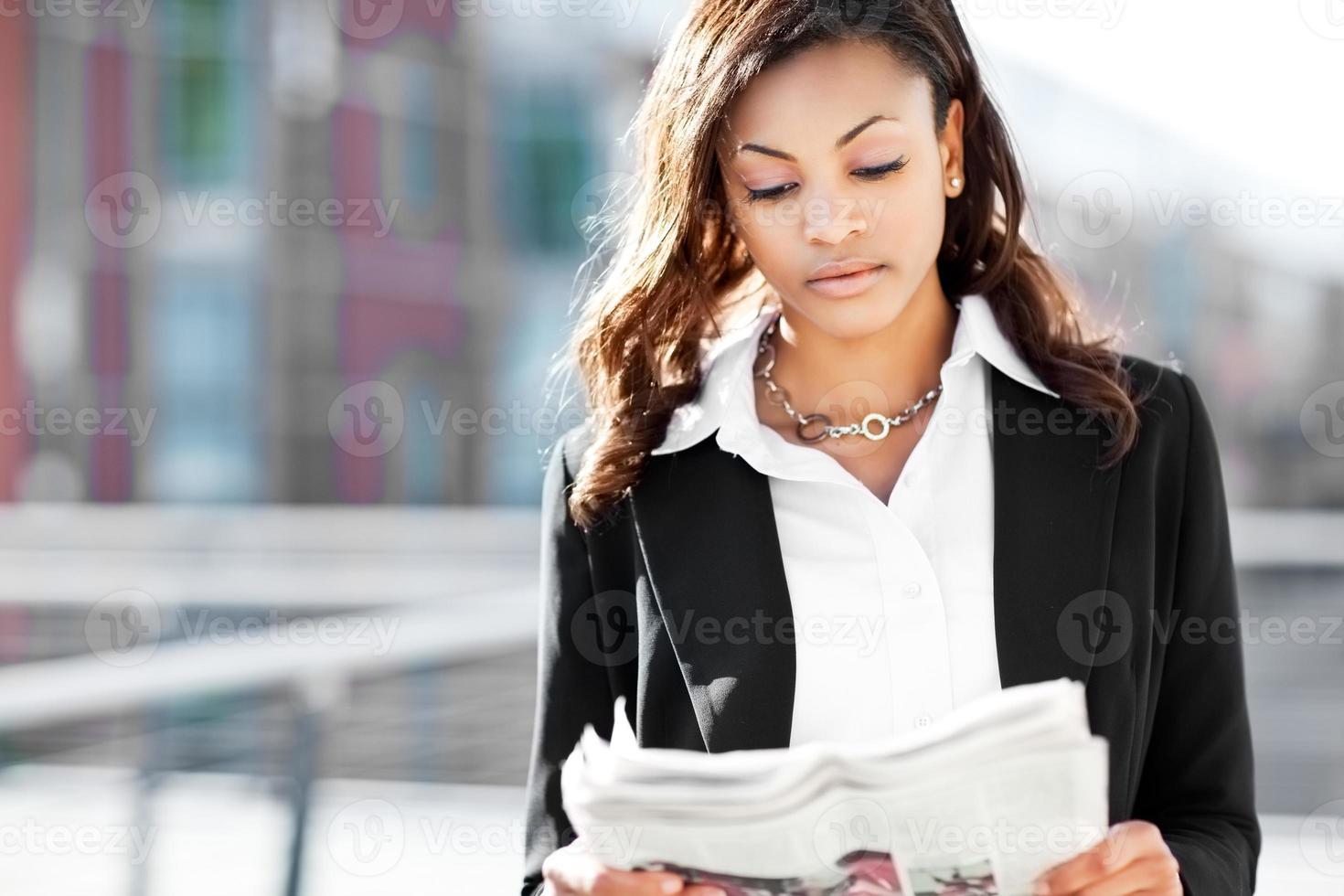 Black businesswoman reading newspaper photo