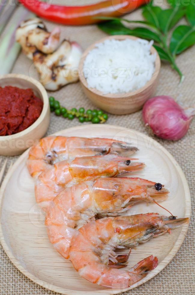 spices in bowl and prawn on sackcloth background photo