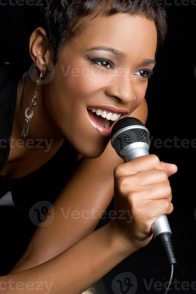Close-up picture of a woman singing in to a microphone photo