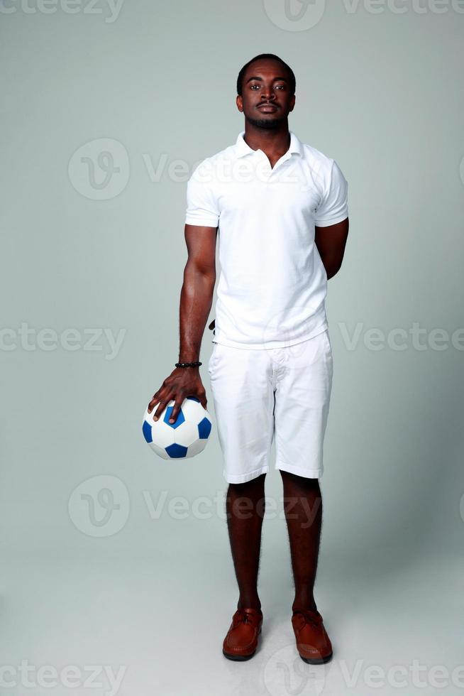 homme africain sérieux debout avec ballon de foot photo