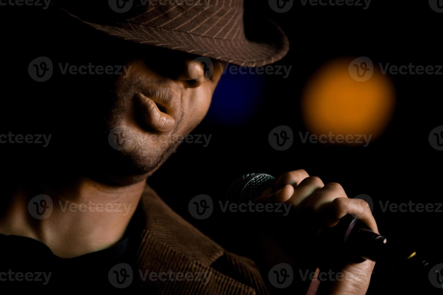 African American male singer wearing a fedora at microphone photo