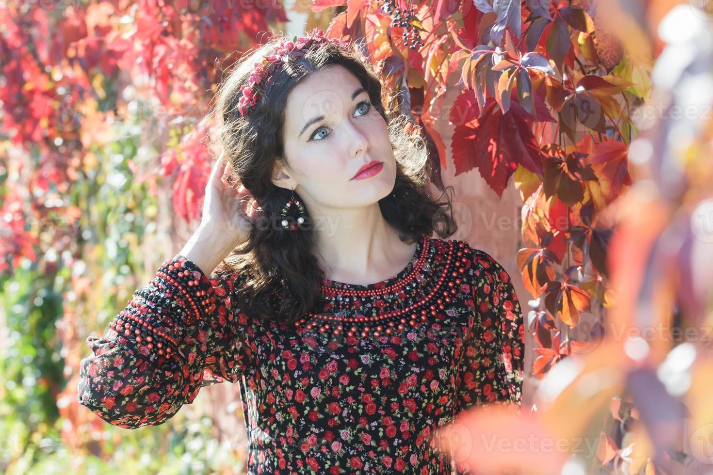rêverie automne fille avec couronne à fond floral rouge photo