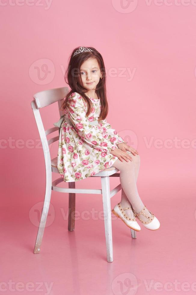 Smiling baby girl sitting on chair photo