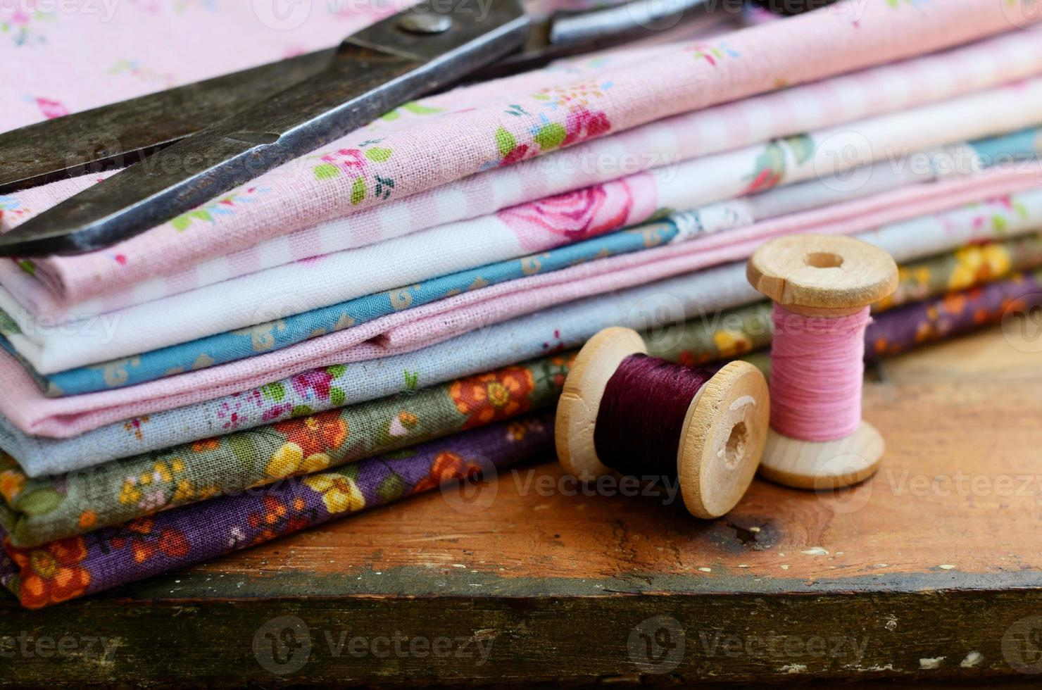 Set of different fabrics, wooden thread spools and tailor scissors photo