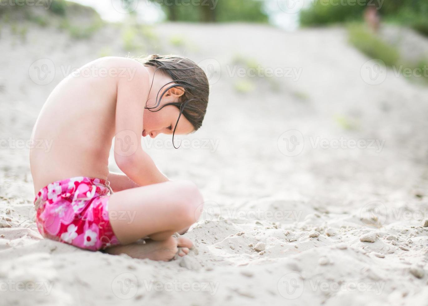 kleines Mädchen sitzt auf Sand am Strand foto