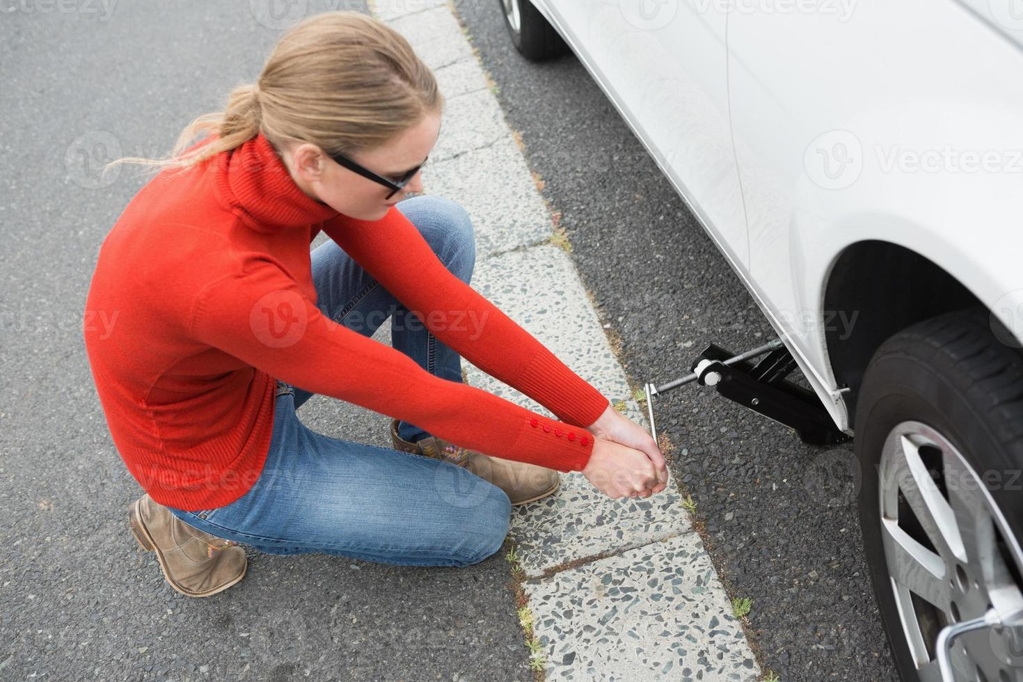 Woman replacing tire photo