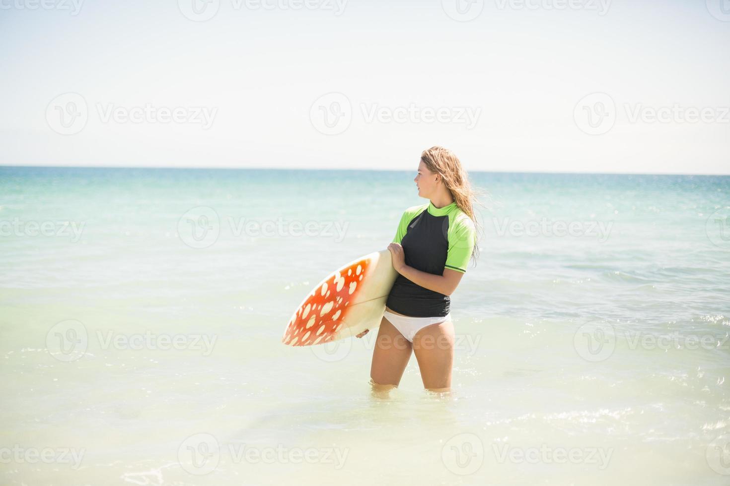 Jolie femme blonde tenant une planche de surf dans l'eau photo