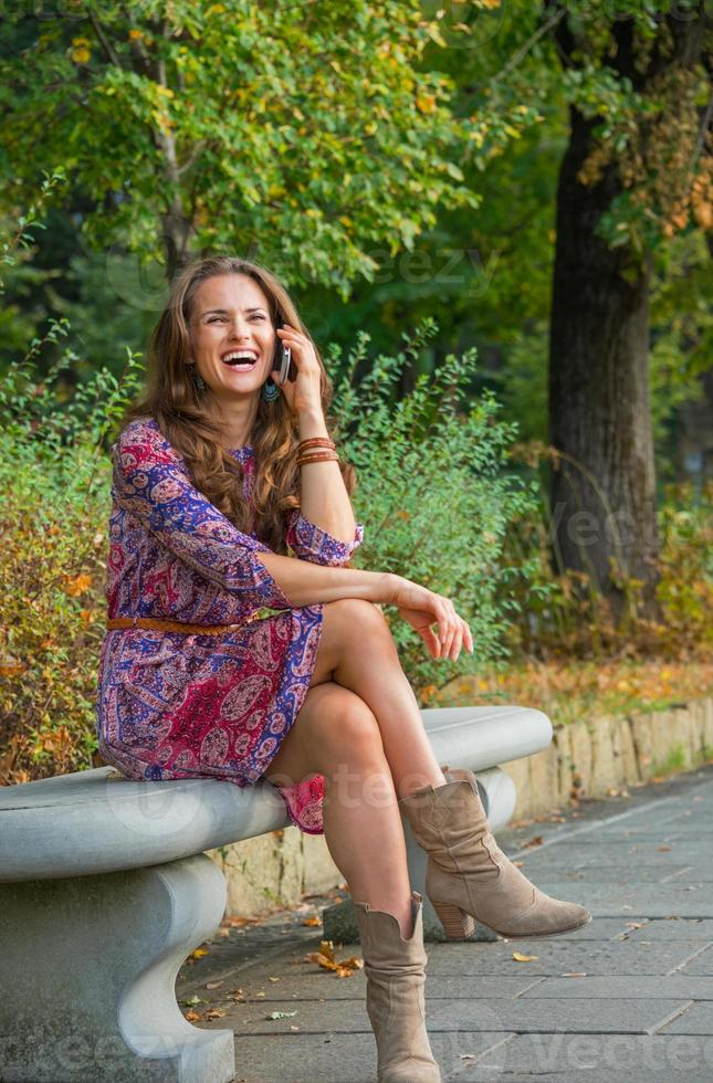 smiling young woman talking cell phone in city park photo