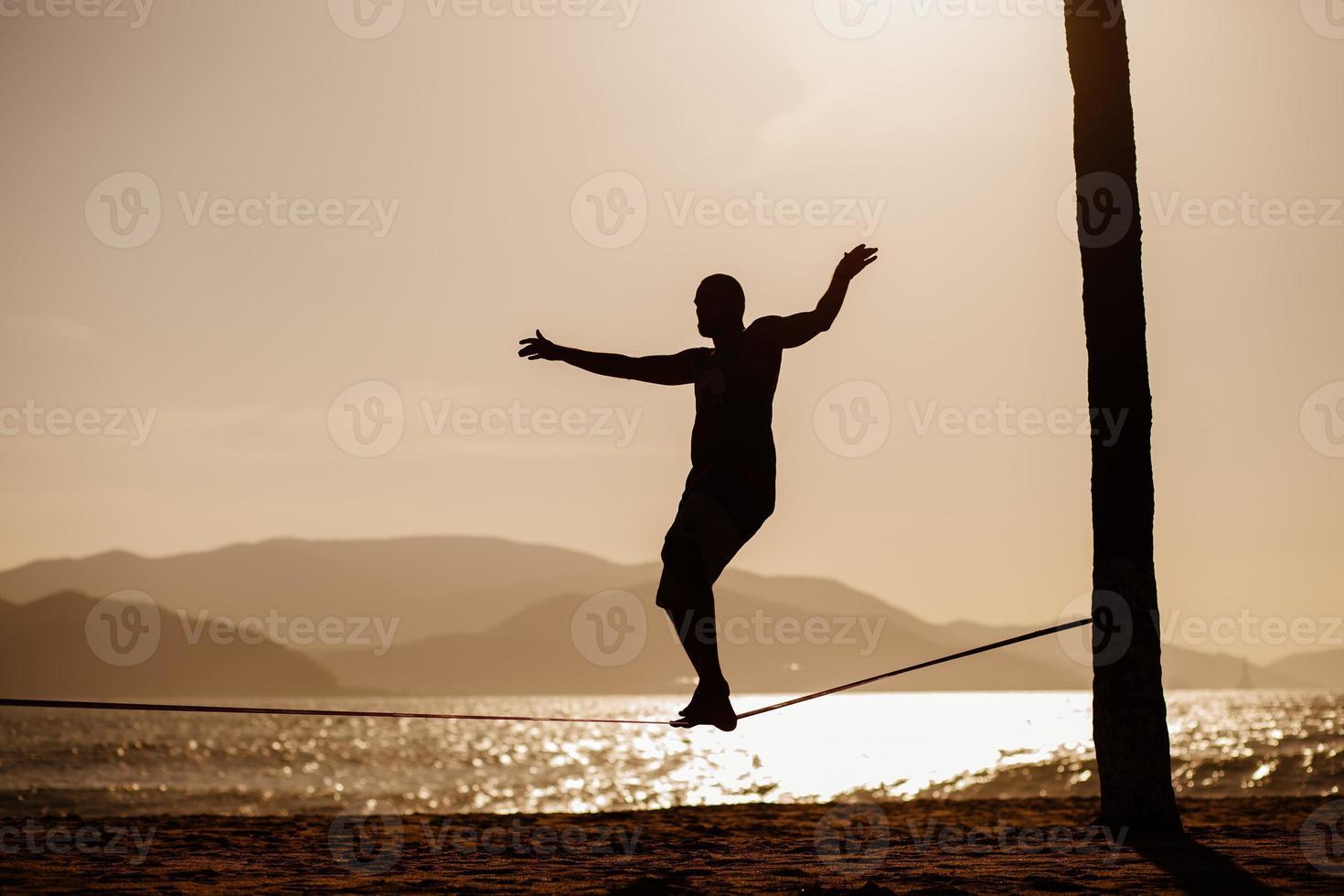 Teenage en équilibre sur slackline avec vue sur la mer photo