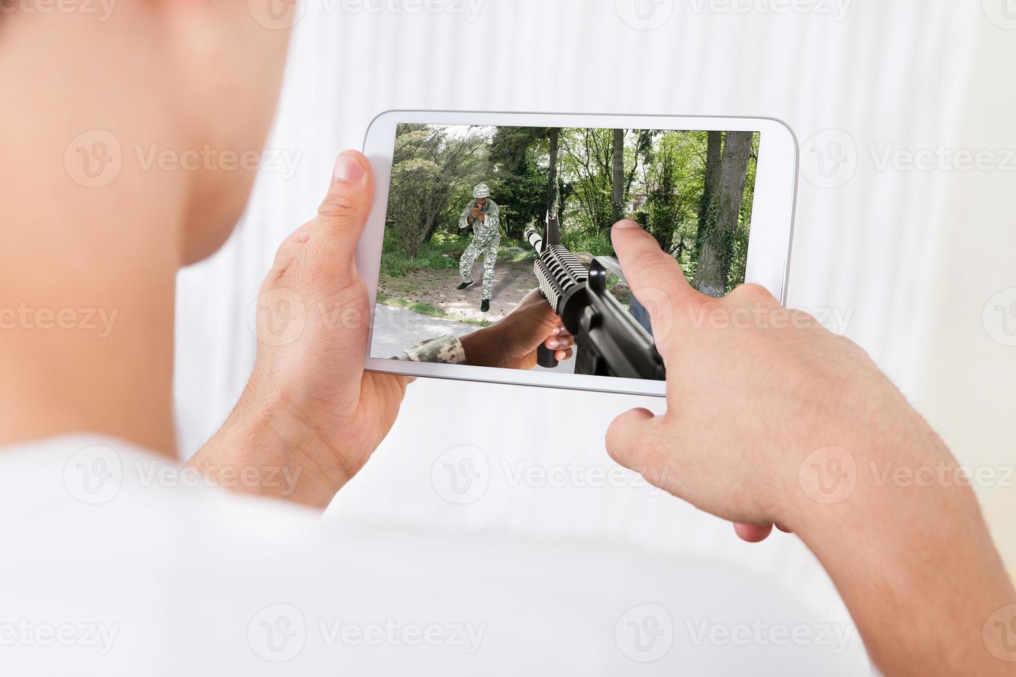 Hombre jugando juegos de acción en tableta digital en casa foto