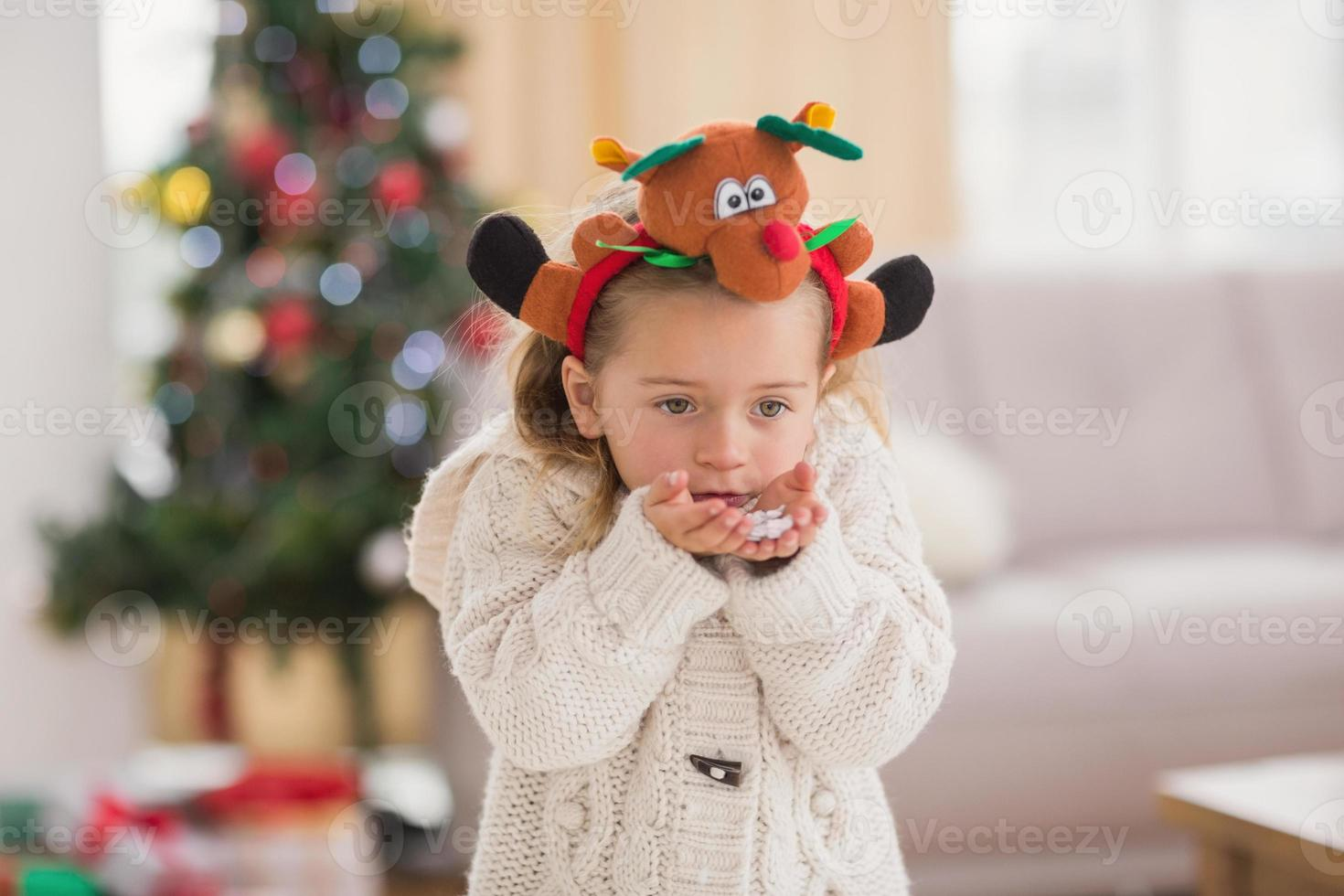 Festive little girl blowing over hands photo