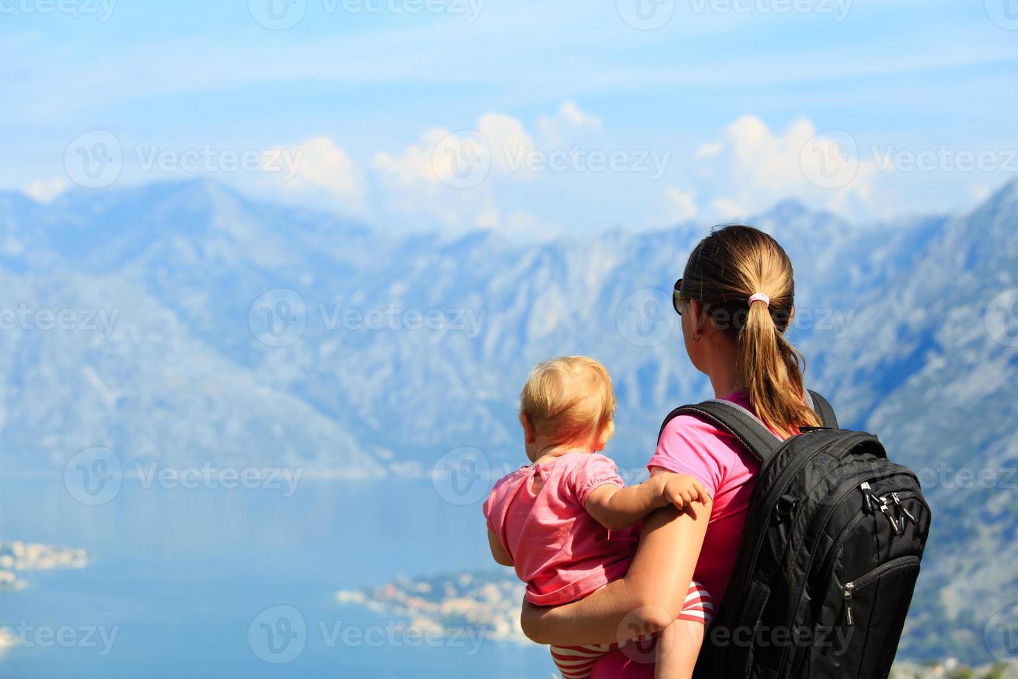 mãe com filha olhando para as montanhas foto
