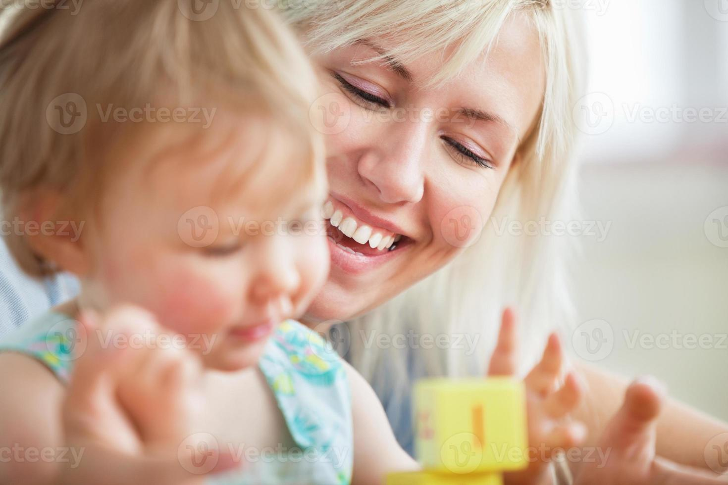 Close-up of a bright mother playing with her daughter photo