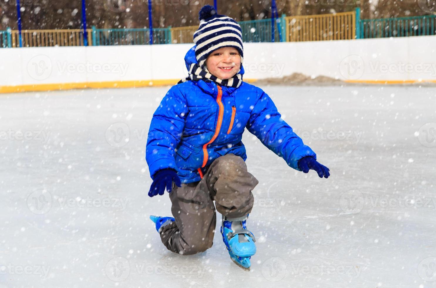 süßer kleiner Junge, der im Winter Skaten lernt foto