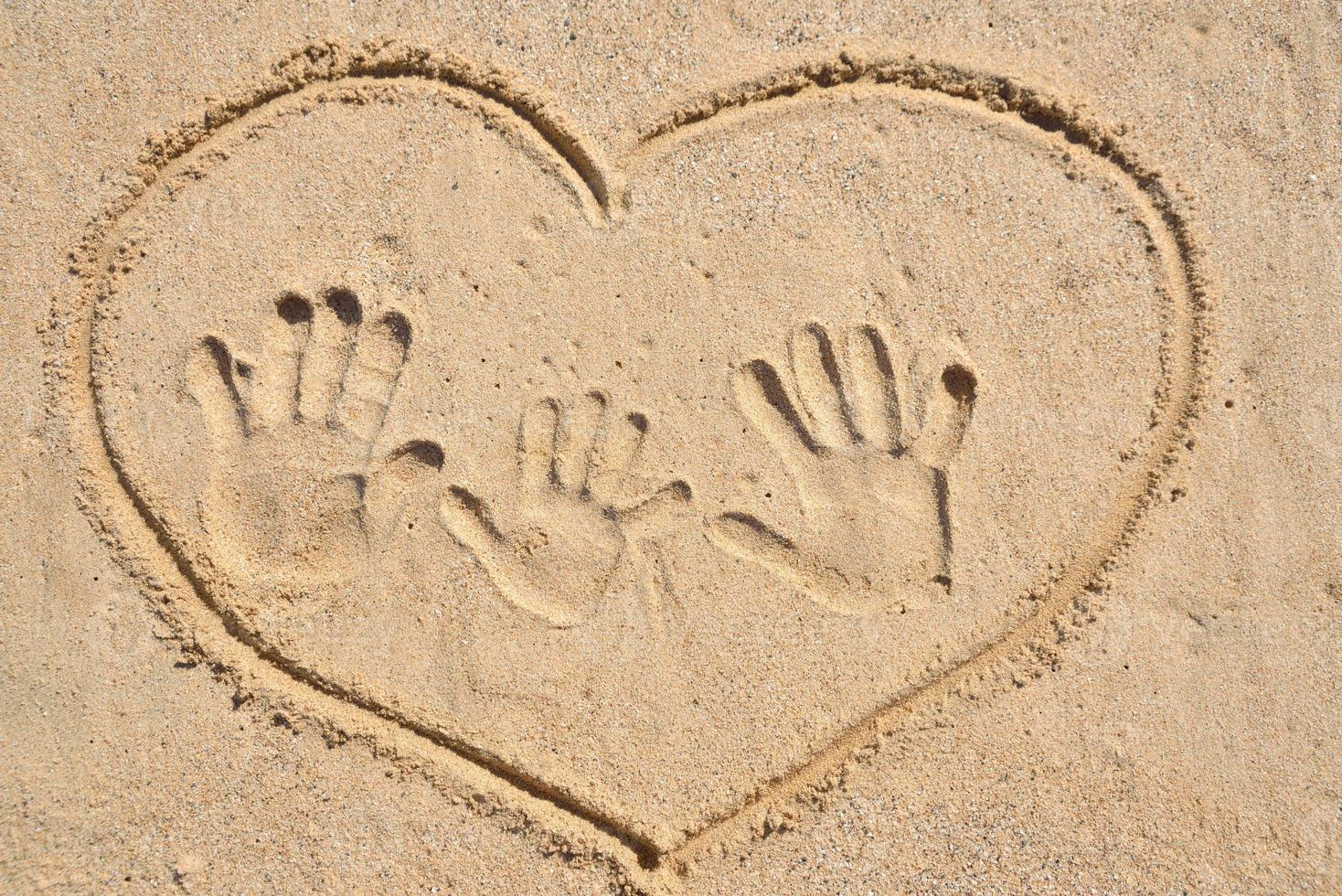 Drawing heart with family hand print on sand. photo