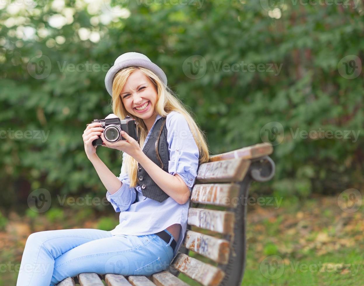 fille souriante hipster avec appareil photo rétro assis sur un banc