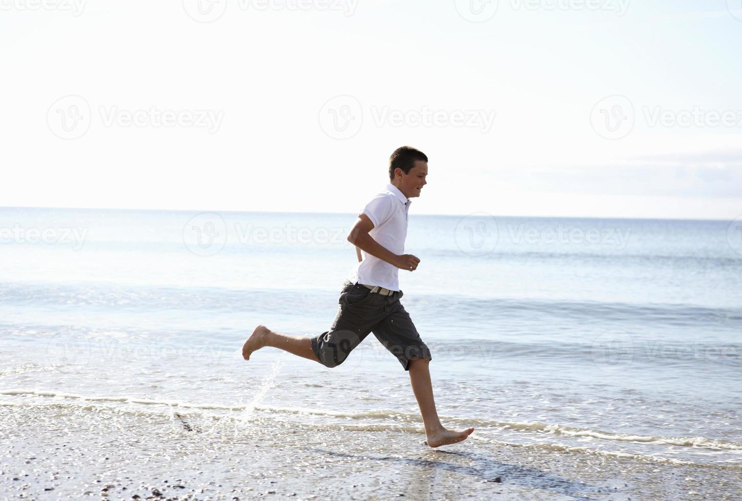 Boy running barefoot on beach photo