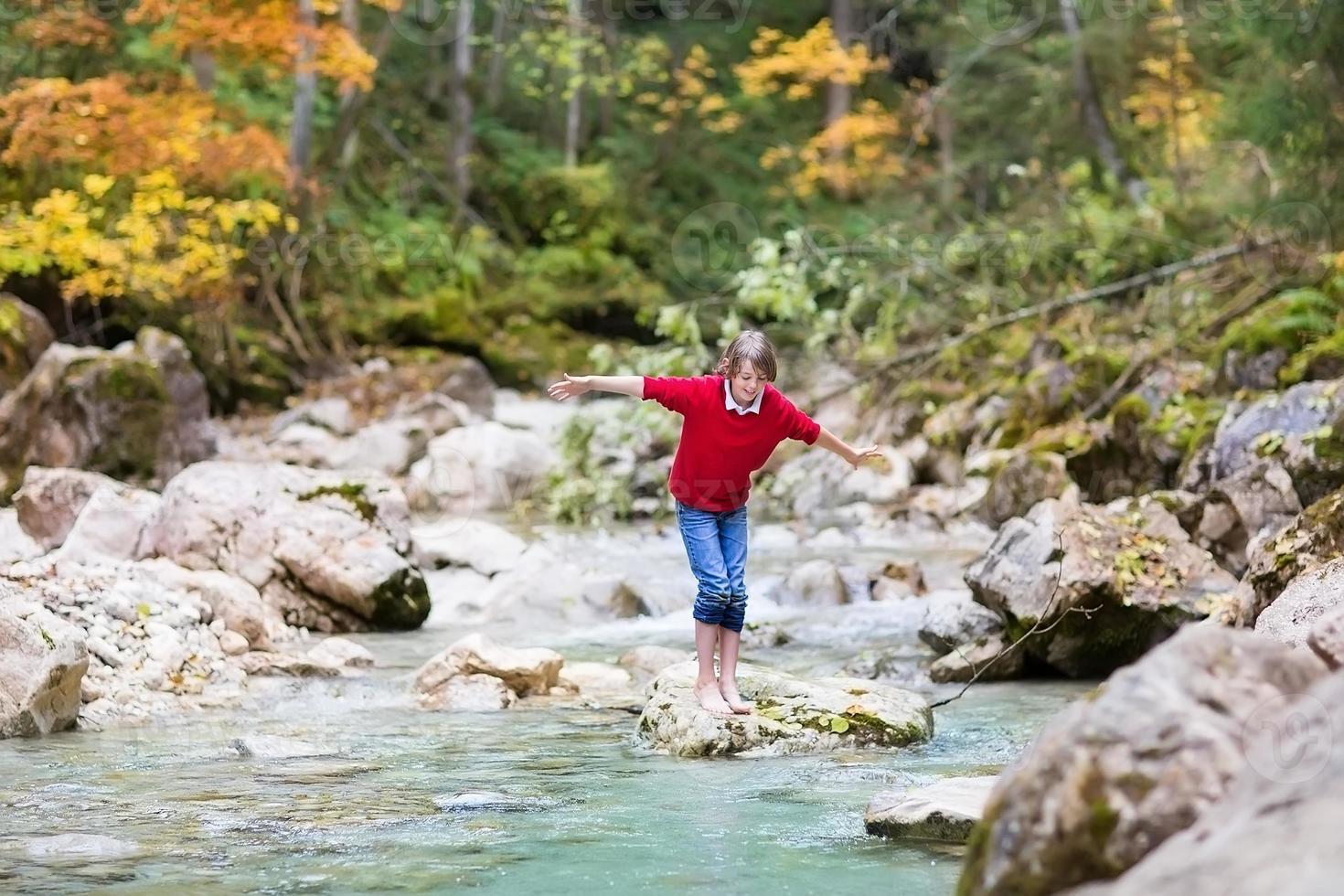 sorridente menino feliz cruzando um rio de montanha selvagem pulando sobre pedras foto