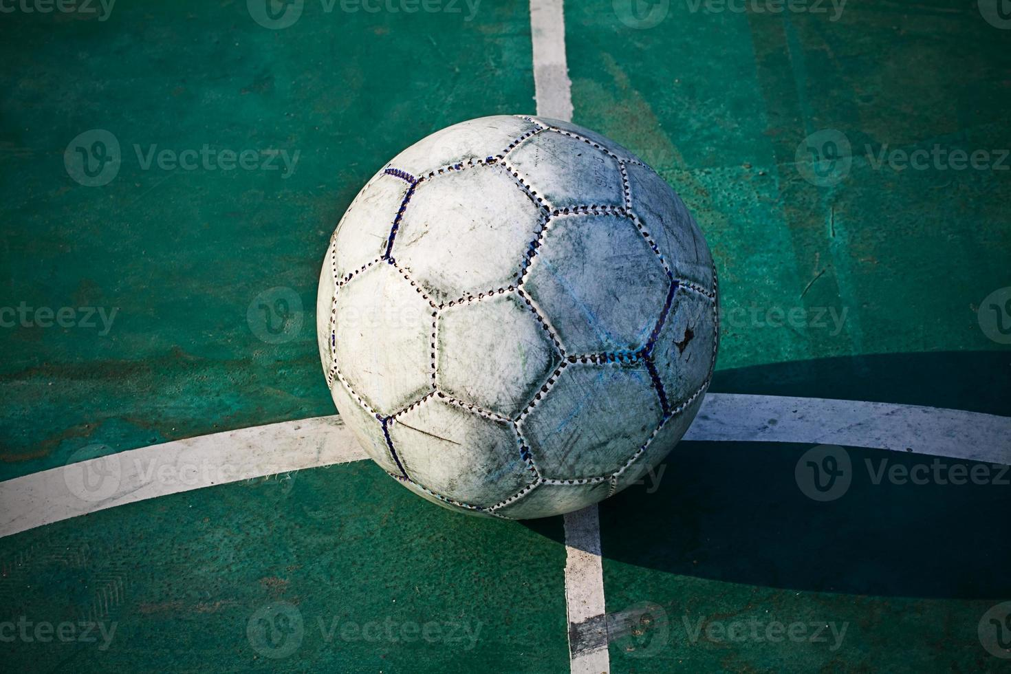 Old used football or soccer ball on cracked asphalt photo