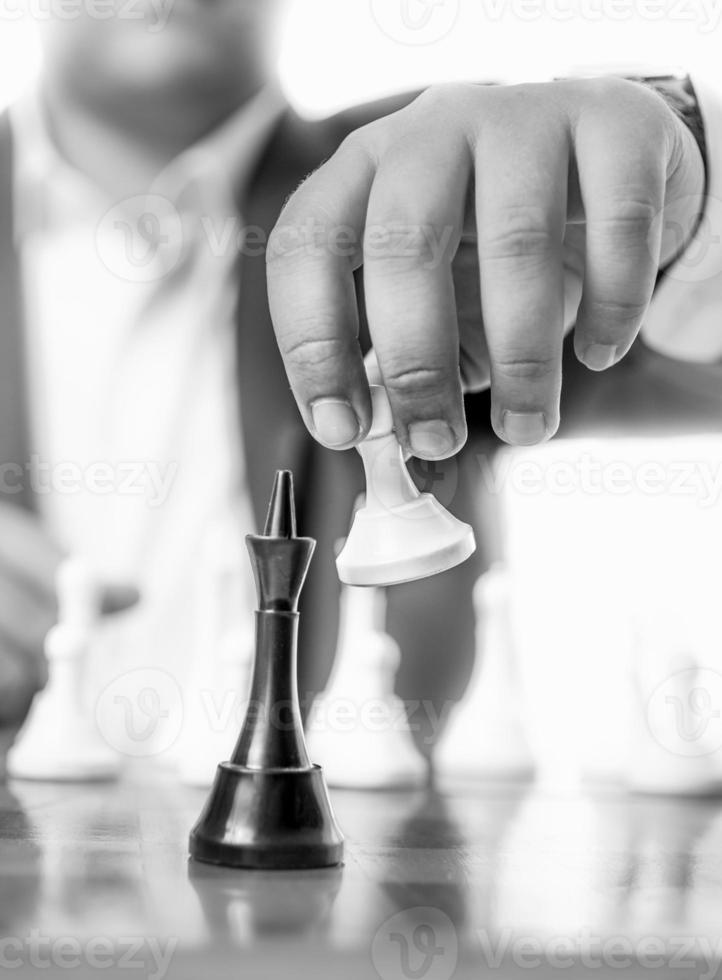 Monochrome shot of businessman beating chess king with pawn photo