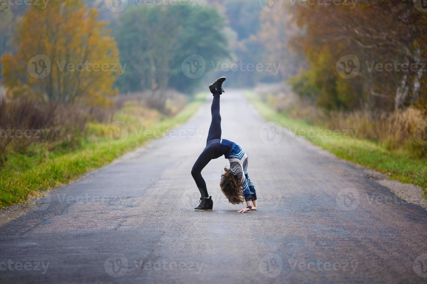 Young girl makes splits on the road photo