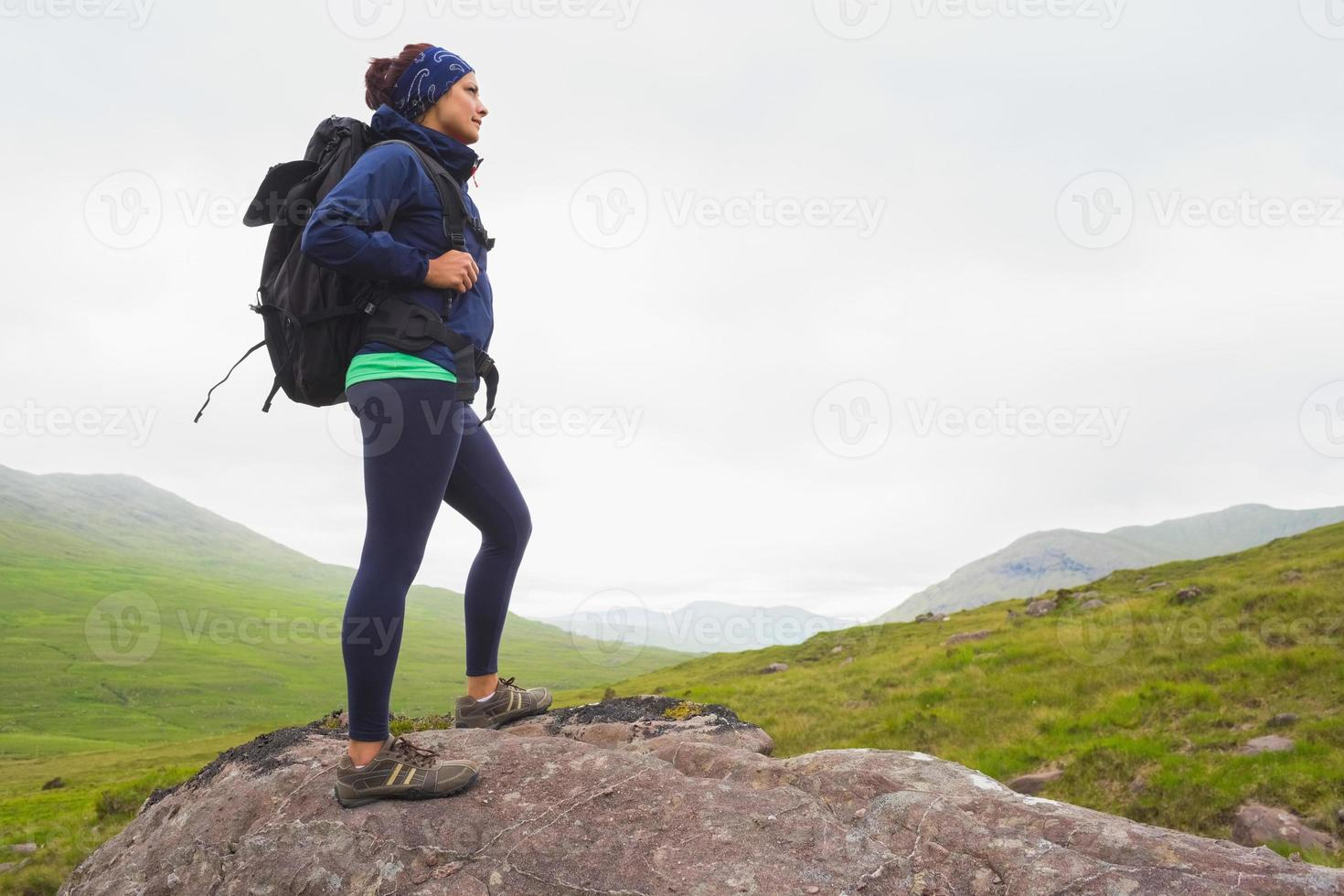 Woman standing on rock admiring the view photo
