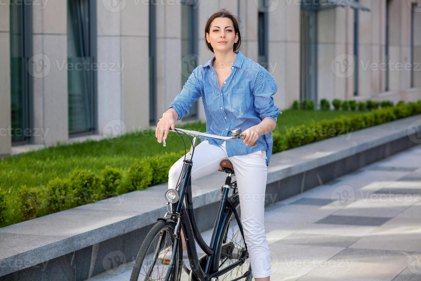Pretty girl sitting on a bicycle at street photo