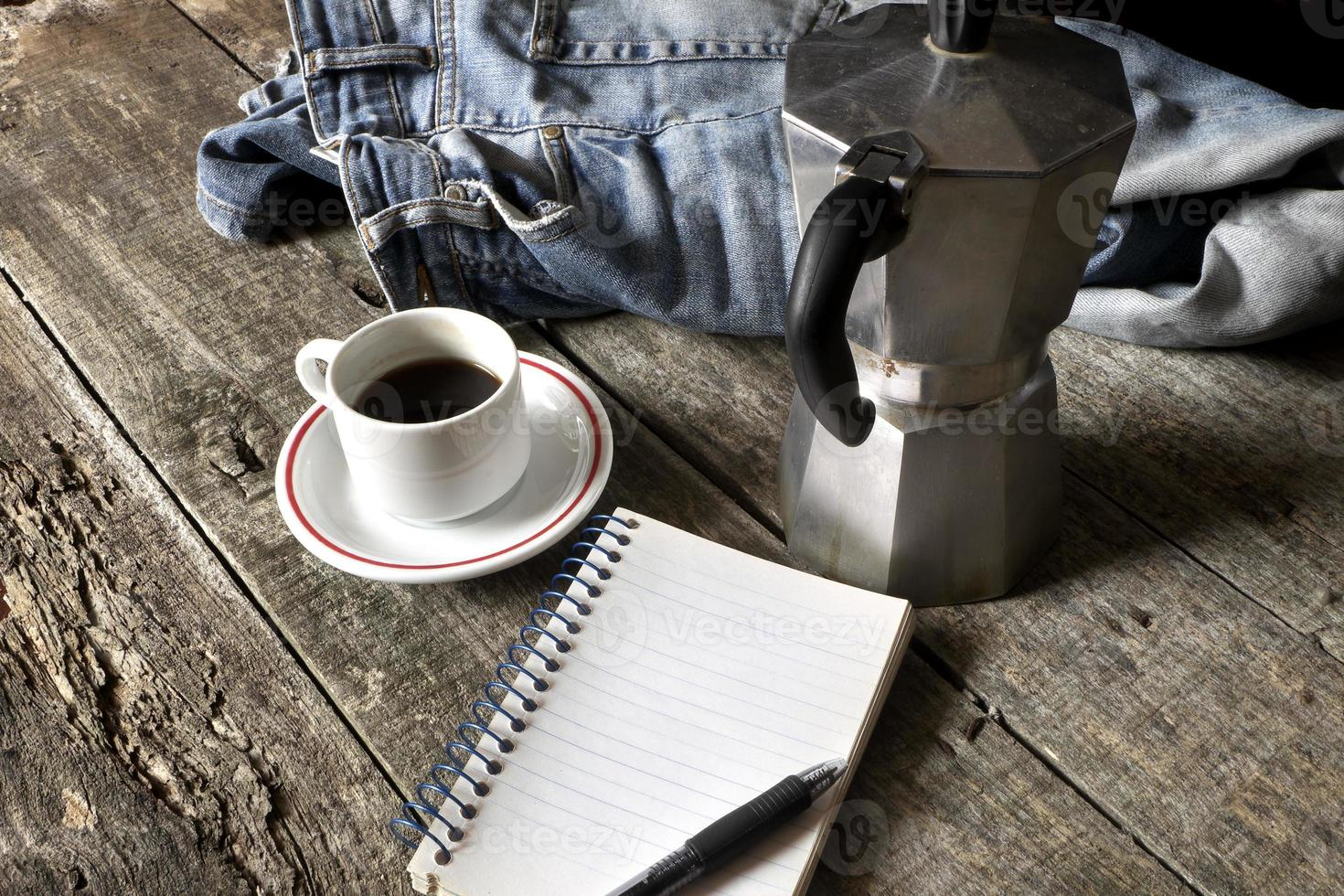 Cup of coffee, espresso maker, notepad and dirty jeans photo