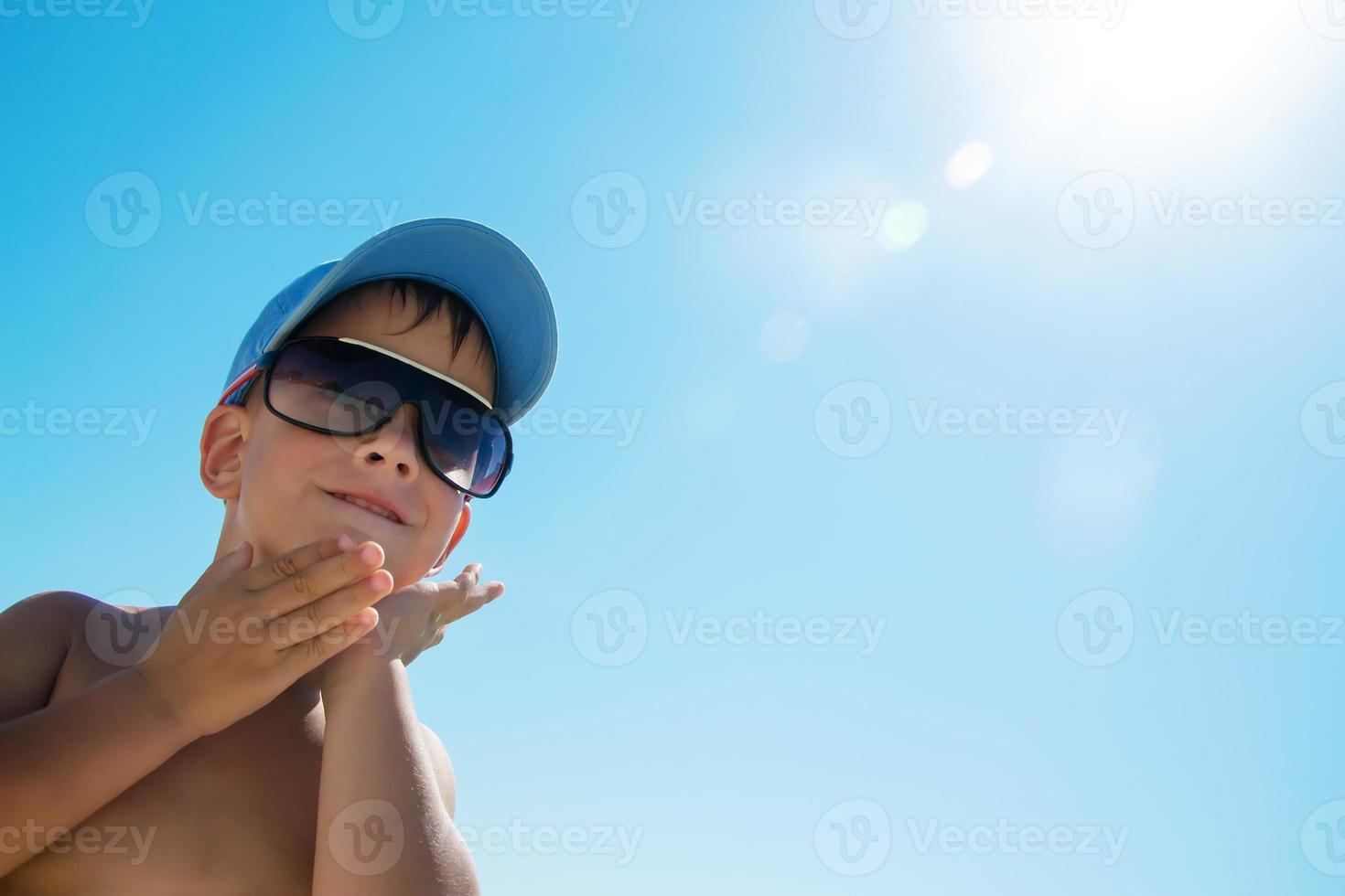 bel bambino che indossa il berretto blu sulla spiaggia foto