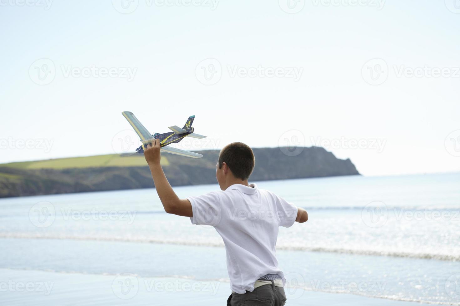 jongen vliegend speelgoed vliegtuig op strand foto