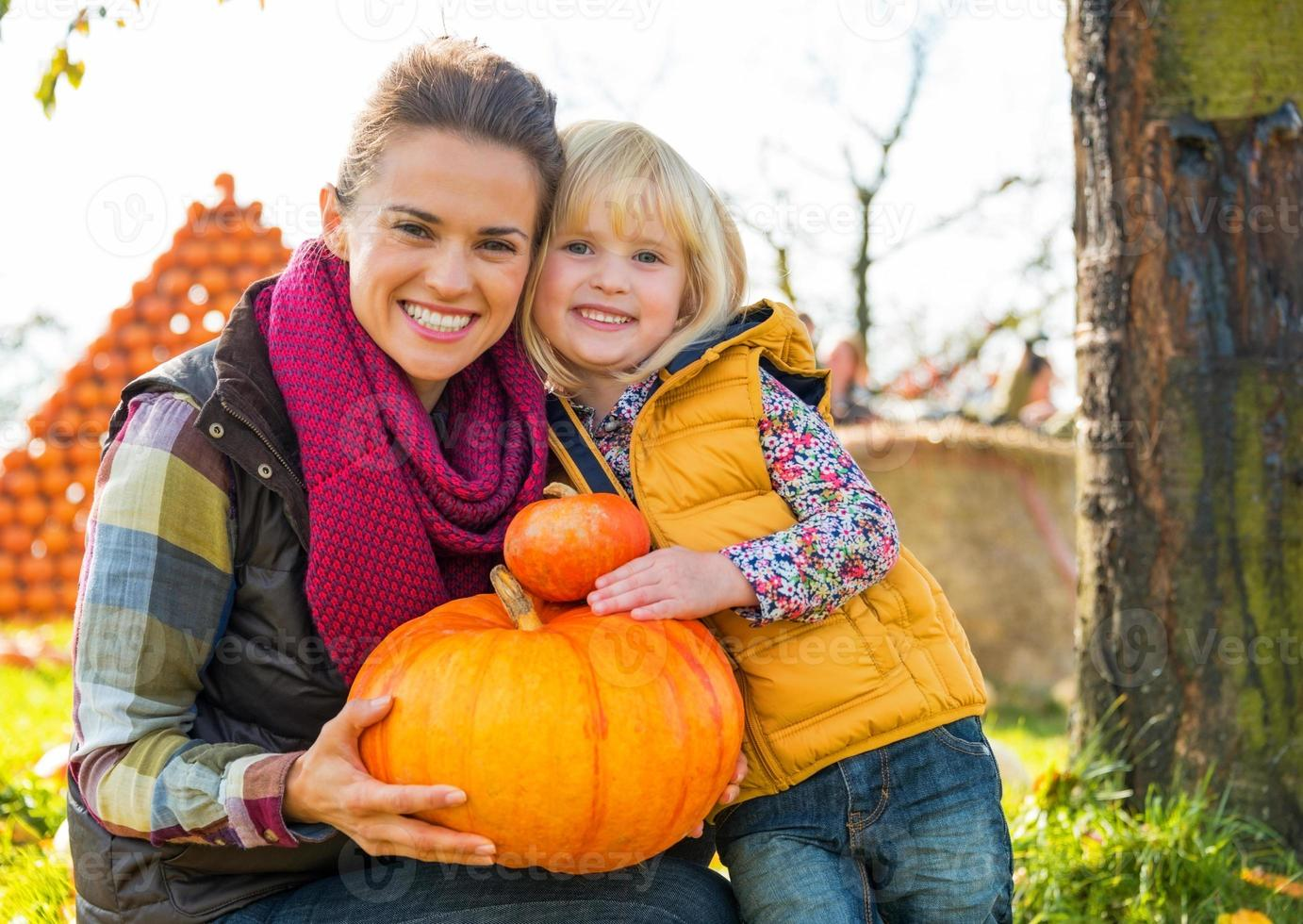 portrait of happy mother and child holding pumpkin photo