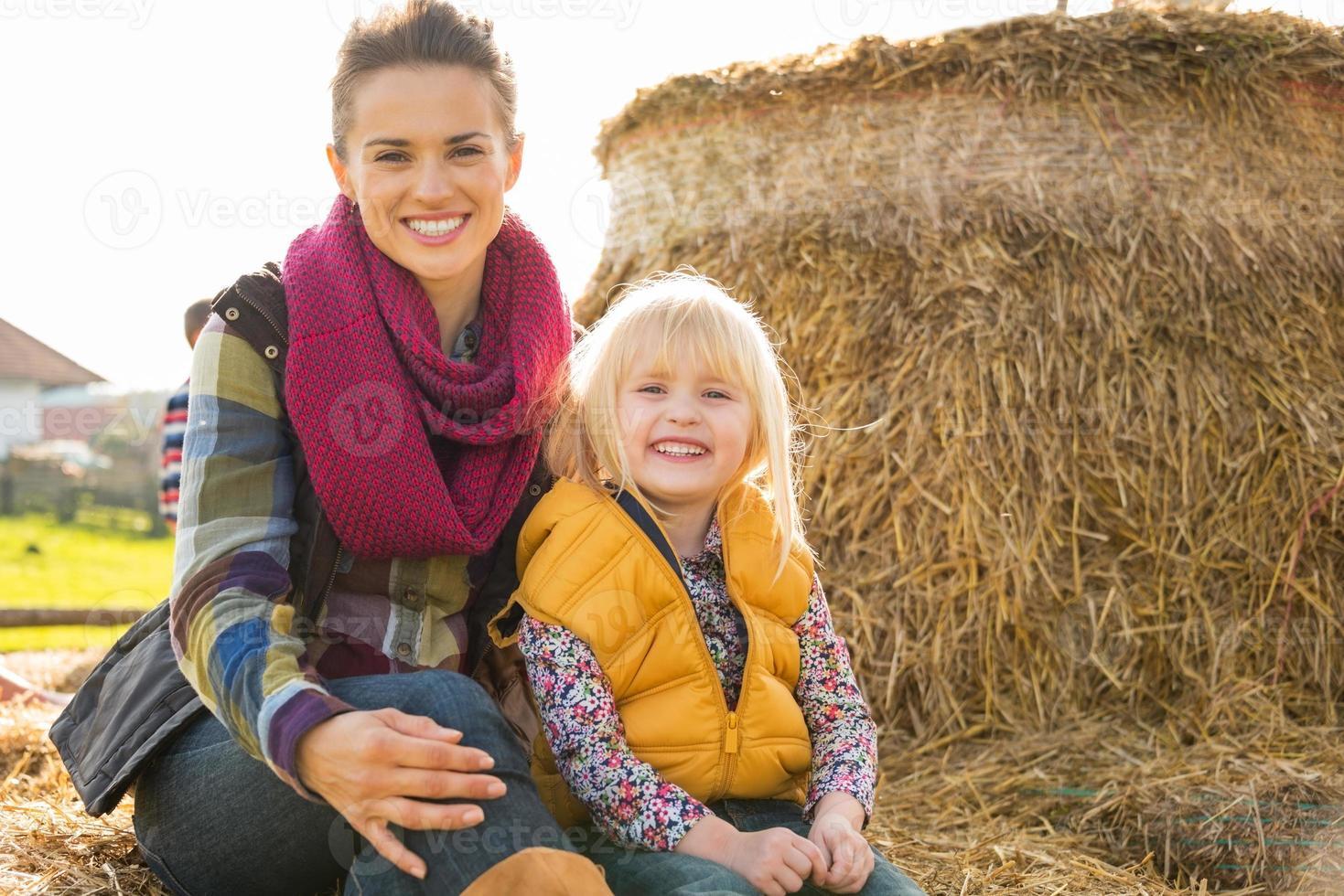 Portrait de l'heureuse mère et enfant assis sur une botte de foin photo