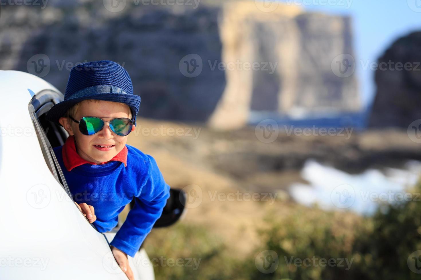 heureux petit garçon voyage en voiture en vacances d'été photo