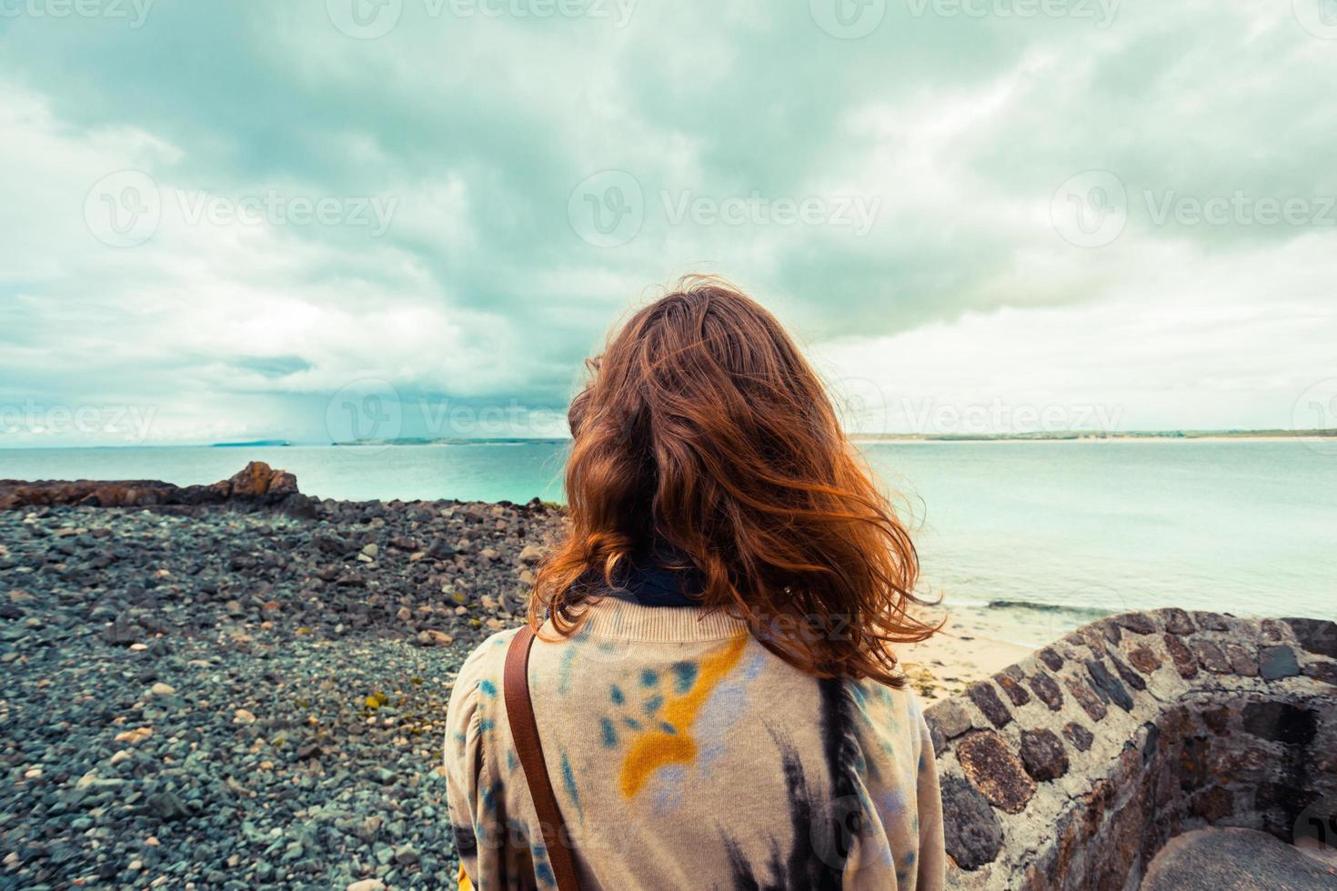 Young woman standing on the coast photo