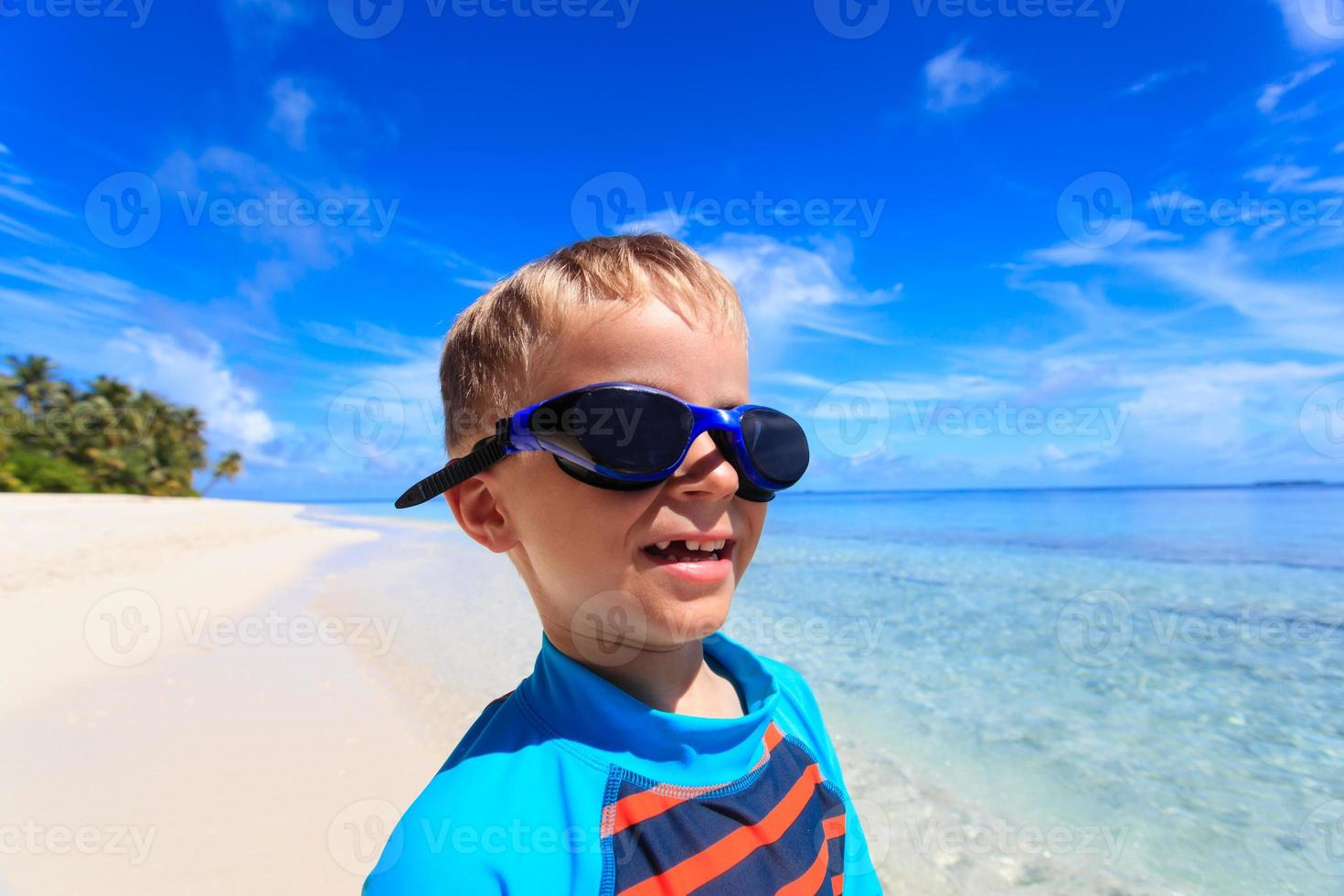 happy boy in swimming goggles at the beach photo