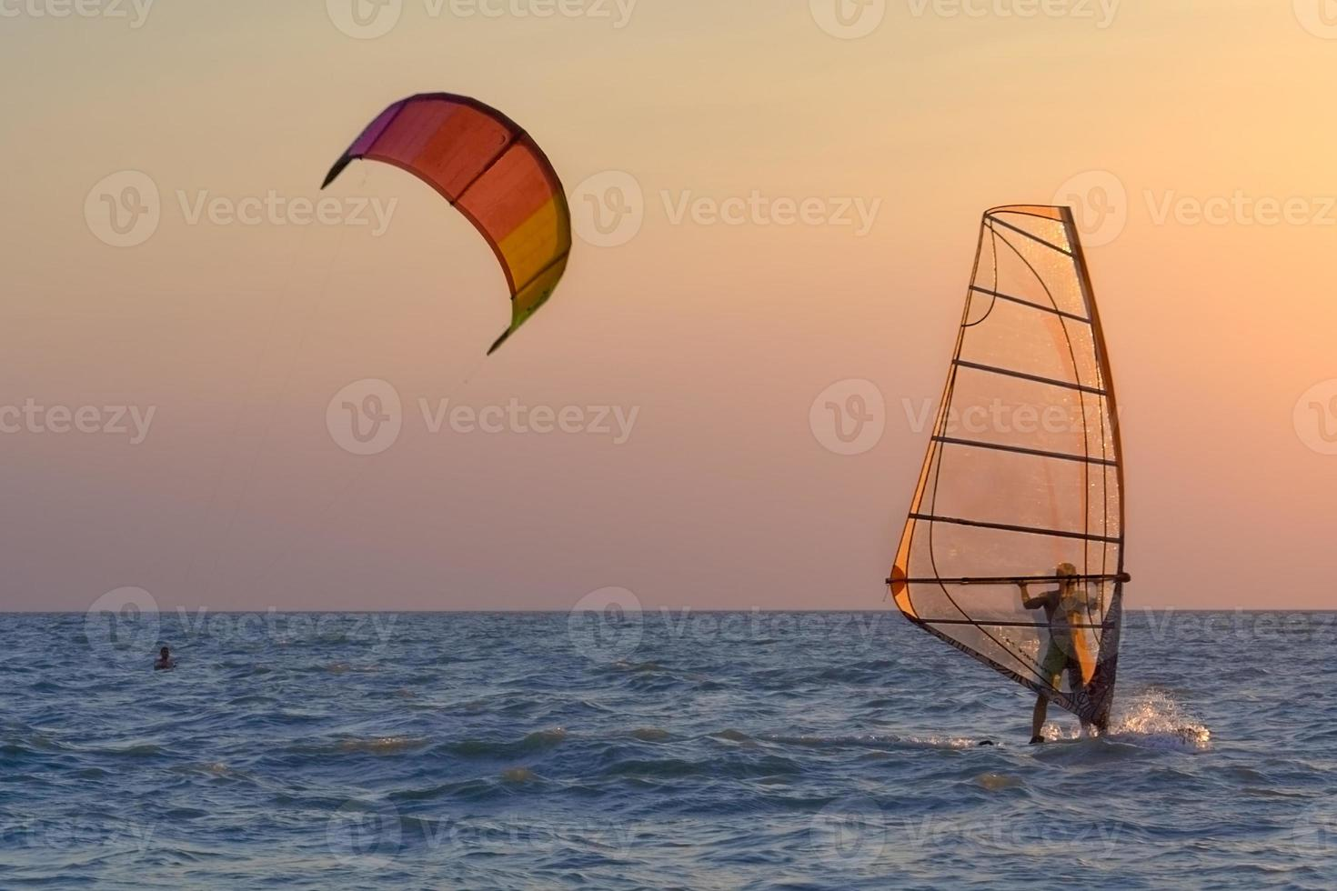Kite-surfing and windsurfing at the sunset photo